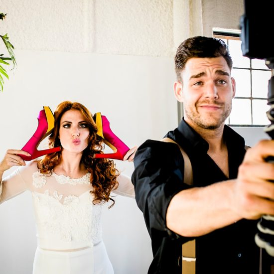 Bruid met roze schoenen en bruidegom die selfie maakt