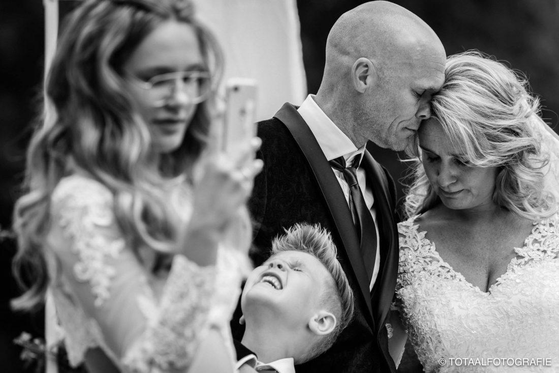 Emotioneel bruidspaar met zoon die omhoog kijkt en dochter die foto maakt van zangeres Maan