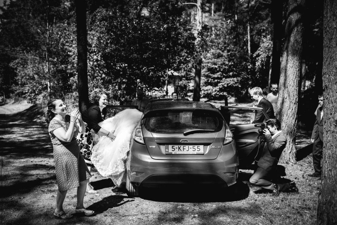 Jurk van bruid wordt in de auto gepropt