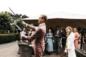 Bruidegom sabreert champagne