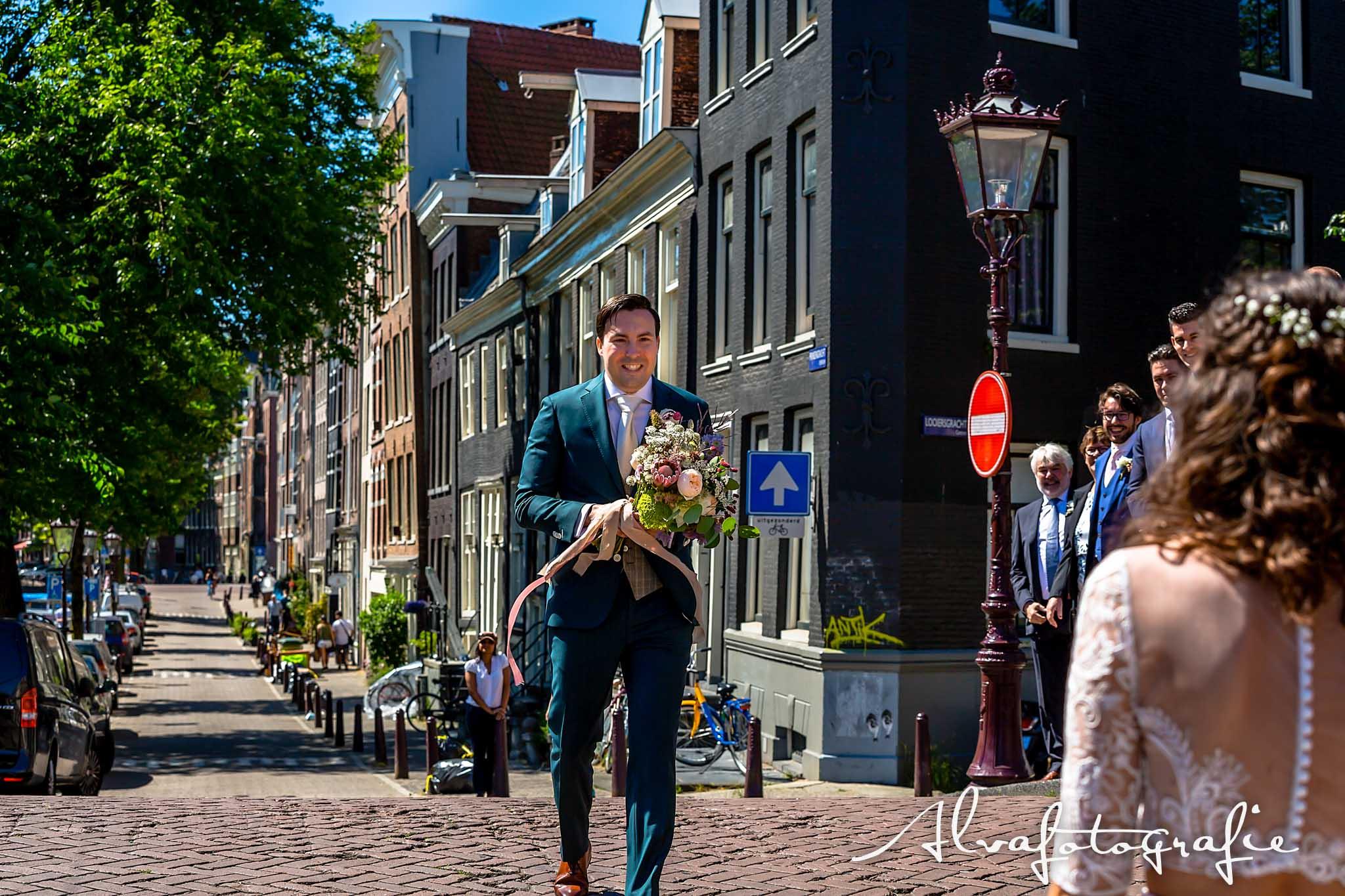 Bruiloft Maren en Tim Alvafotografie bruidegom komt aan met boeket bij bruid grachten Amsterdam