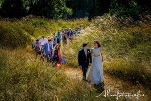 Bruiloft Maren en Tim Alvafotografie bruidspaar loopt heuvel op met gasten Paviljoen Puur