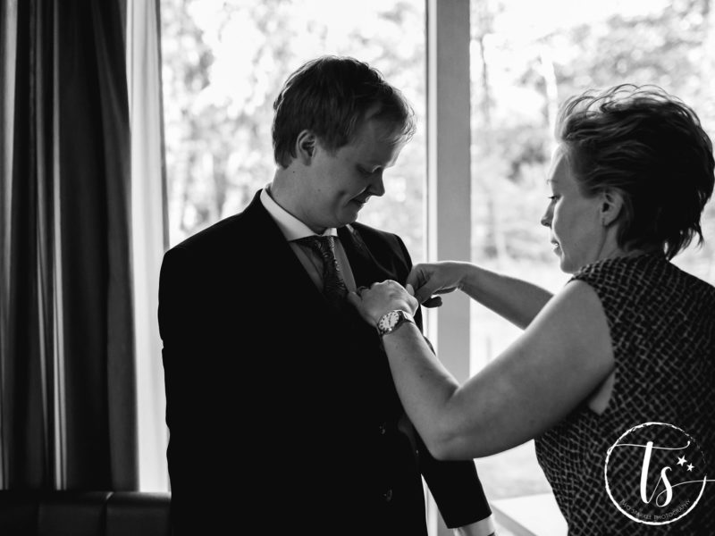 Ceremoniemeester van Stralend Middelpunt helpt de bruidegom met de corsage, Bruiloft Kim en Ronald, foto Two Sparkle Photography