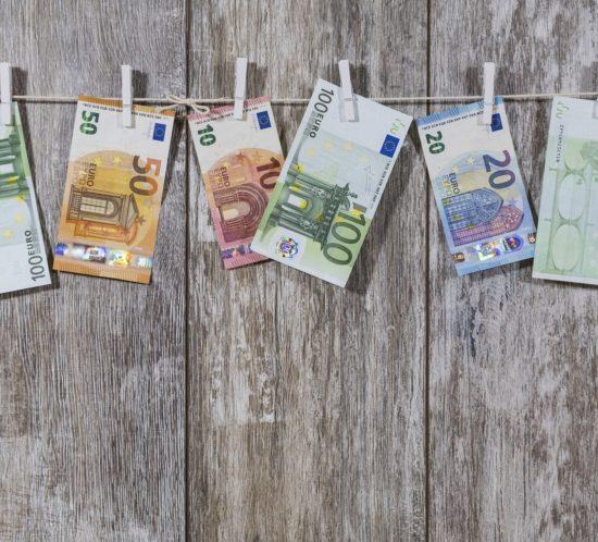 Geld met wasknijpers aan een waslijn op een houten bord als cadeau voor bijvoorbeeld een bruiloft