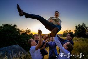 Bruidegom wordt omhoog gegooid door vrienden, foto Alvafotografie