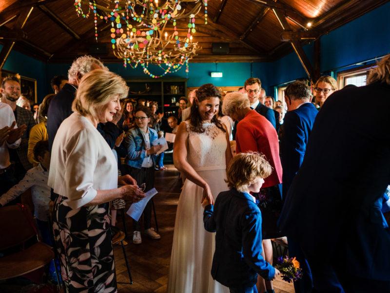 Bruidspaar loopt naar voren met kinderen tijdens ceremonie bij Stayokay Gorssel Foto Eline Bon Fotografie