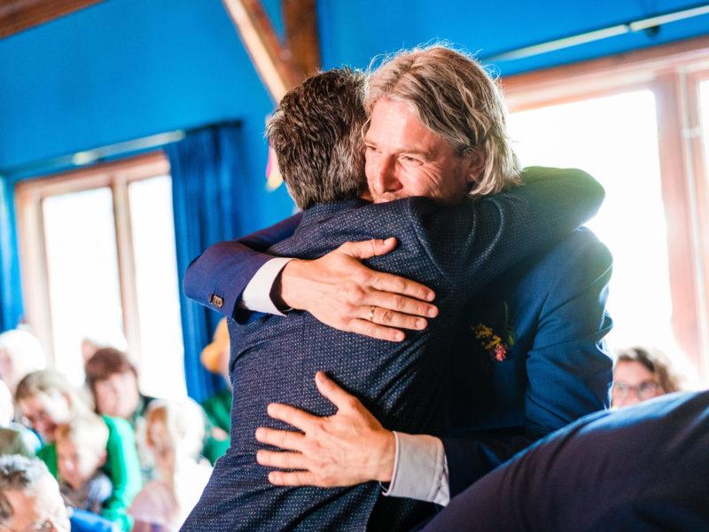 Bruidegom knuffelt vriend bij Stayokay Gorssel Foto Eline Bon Fotografie
