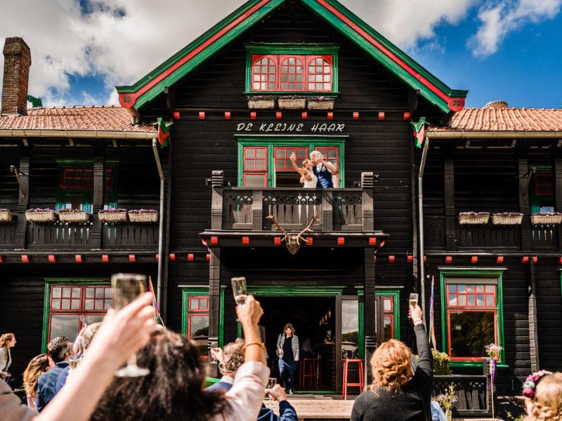 Bruidspaar staat op balkon van Stayokay Gorssel Foto Eline Bon Fotografie
