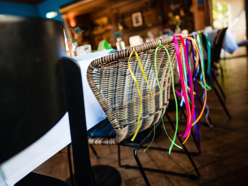 Gekleurde linten aan stoelen van bruidspaar danst bij Stayokay Gorssel Foto Eline Bon Fotografie