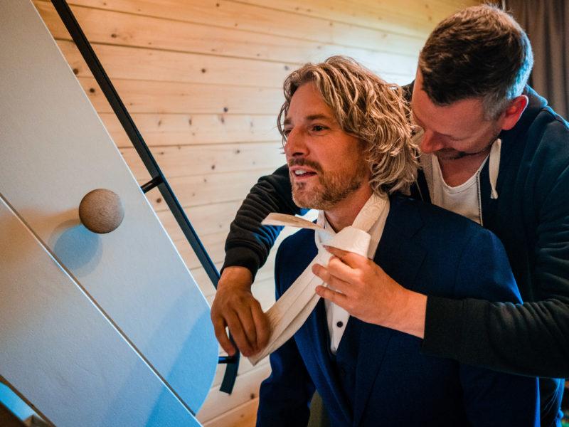 Vriend helpt bruidegom met omknopen van de stropdas bij Stayokay Gorssel Foto Eline Bon Fotografie