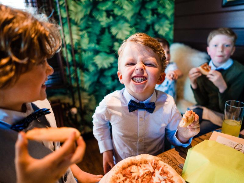 Bruids jonker lacht en eet pizza bij Stayokay Gorssel Foto Eline Bon Fotografie