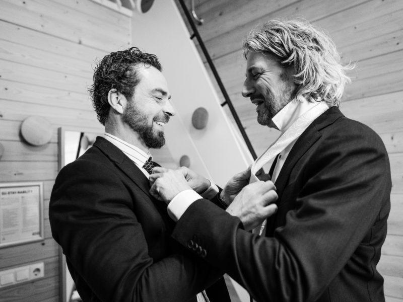 Vriend en bruidegom helpen elkaar met omknopen stropdas bij Stayokay Gorssel Foto Eline Bon Fotografie