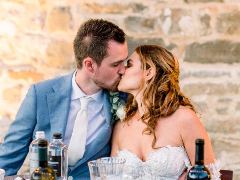 Bruidspaar kust elkaar aan tafel. Foto: Jessica Photography