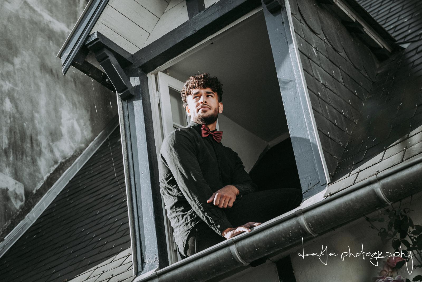 Bruidegom zit in het raam. Foto: D-eYe Photography