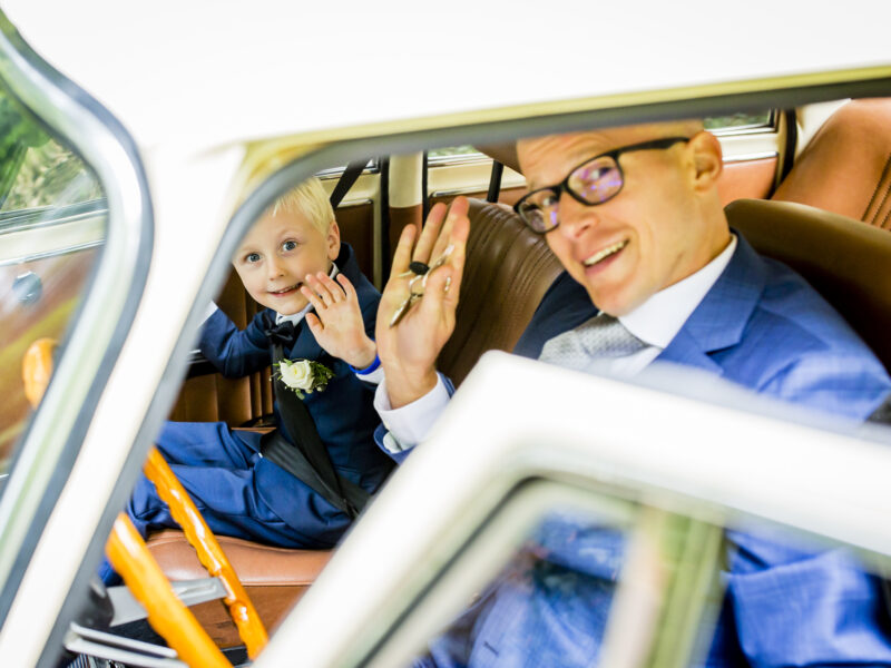 Bruidegom en bruidsjonker zwaaien vanuit auto. Fotograaf Karin Keesmaat van Kijk-Kunst fotografie