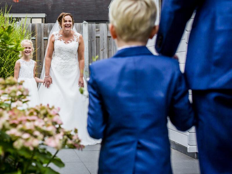 Bruid en bruidsmeisje zien bruidegom en bruidsjonker aankomen. Fotograaf Karin Keesmaat van Kijk-Kunst fotografie
