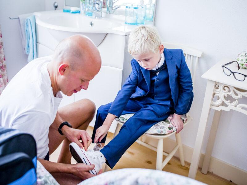 Bruidegom helpt zoon met het aantrekken van zijn schoen. Fotograaf Karin Keesmaat van Kijk-Kunst fotografie