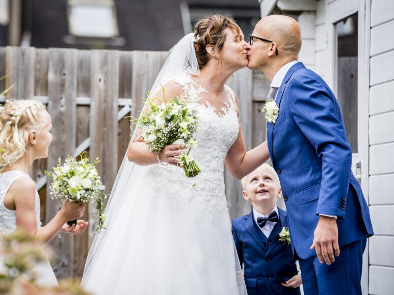 Bruidspaar kust elkaar terwijl bruidsjonker toekijkt. Fotograaf Karin Keesmaat van Kijk-Kunst fotografie