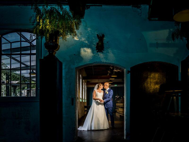 Bruidspaar uitgelicht in deuropening. Fotograaf Karin Keesmaat van Kijk-Kunst fotografie