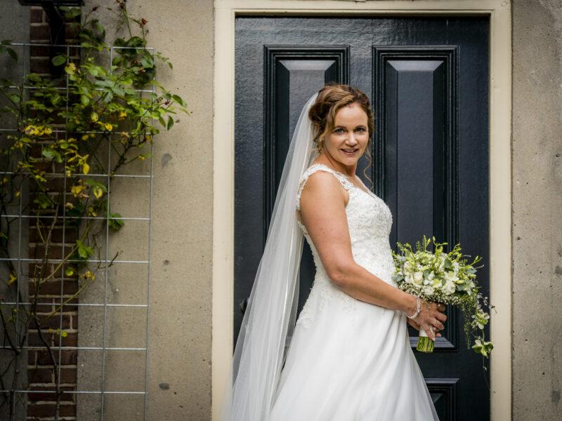 Bruid kijkt in camera voor deur. Fotograaf Karin Keesmaat van Kijk-Kunst fotografie