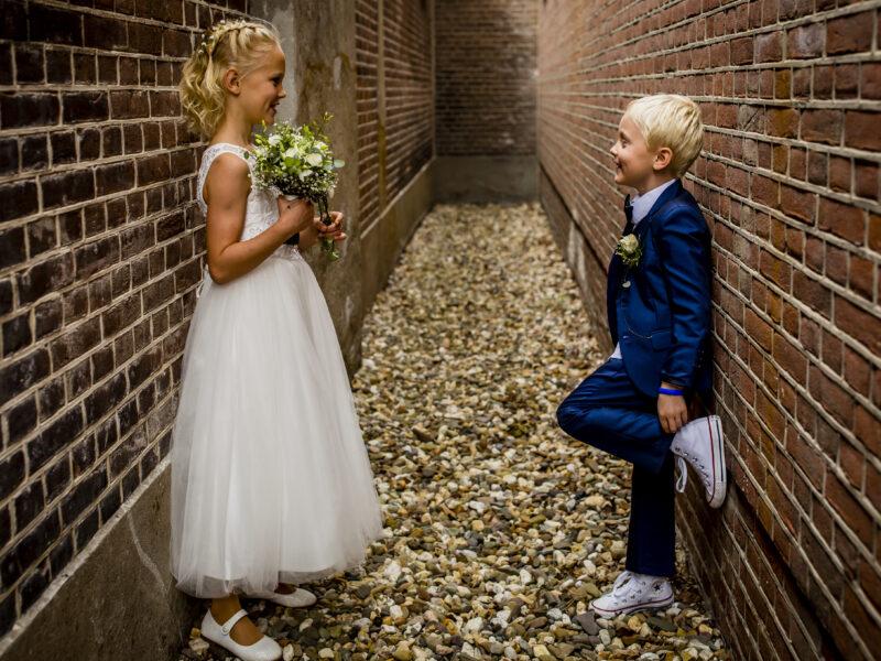 Bruidsmeisje en -jonker in steeg. Fotograaf Karin Keesmaat van Kijk-Kunst fotografie