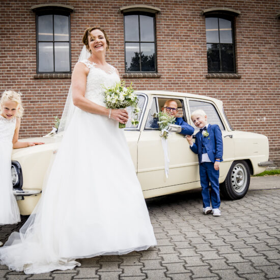 Bruidegom in auto, bruid, bruidsjonker en -meisje ervoor. Fotograaf Karin Keesmaat van Kijk-Kunst fotografie