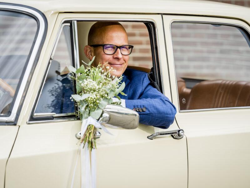 Bruidegom glimlacht vanuit auto. Fotograaf Karin Keesmaat van Kijk-Kunst fotografie