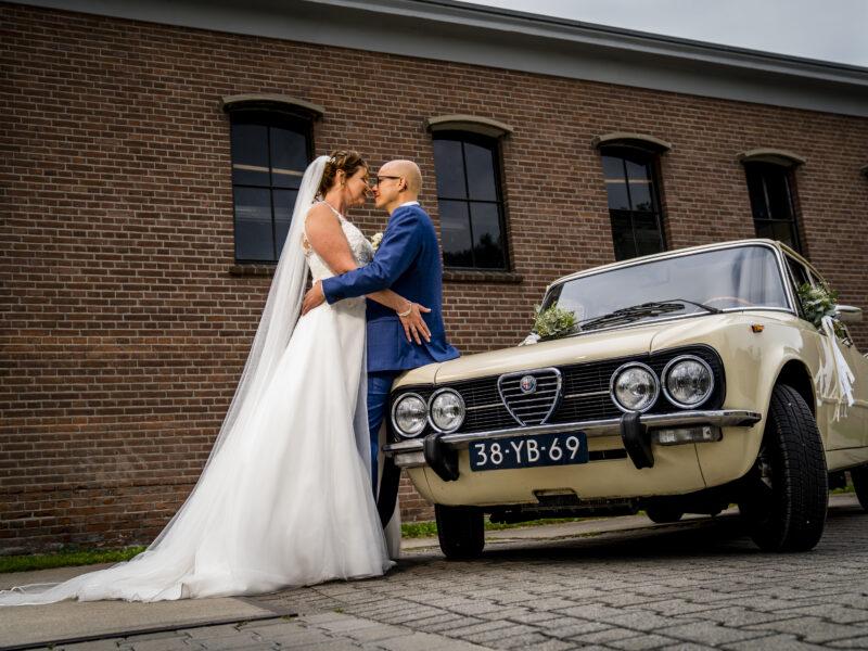 Bruidspaar pakt elkaar vast tegen een oude Alfa Romeo Giulia. Fotograaf Karin Keesmaat van Kijk-Kunst fotografie