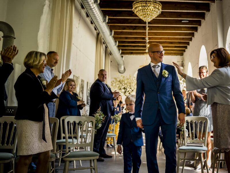 Bruidegom loopt met bruidsjonker naar voren bij de ceremonie. Fotograaf Karin Keesmaat van Kijk-Kunst fotografie