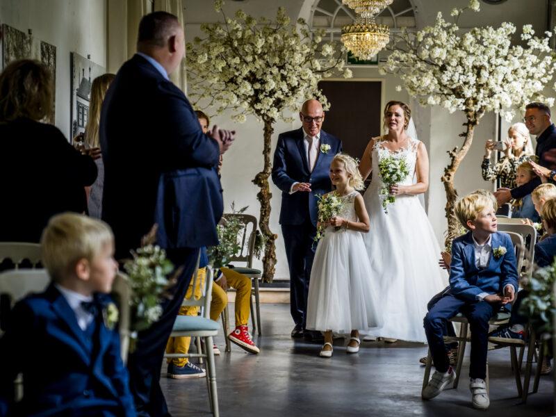 Bruid en vader lopen met bruidsmeisje naar voren. Fotograaf Karin Keesmaat van Kijk-Kunst fotografie