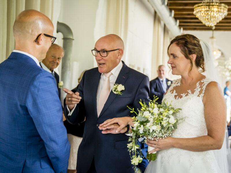 Vader van de bruid geeft haar weg aan de bruidegom. Fotograaf Karin Keesmaat van Kijk-Kunst fotografie