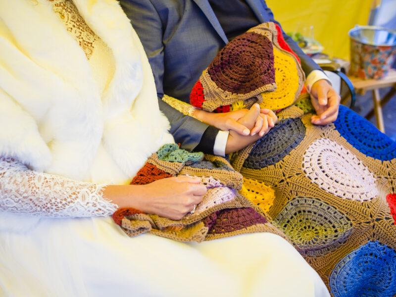 Bruid en bruidegom houden elkaars hand vast. Fotograaf Karin Keesmaat van Kijk-Kunst fotografie en Renske Kleverwal