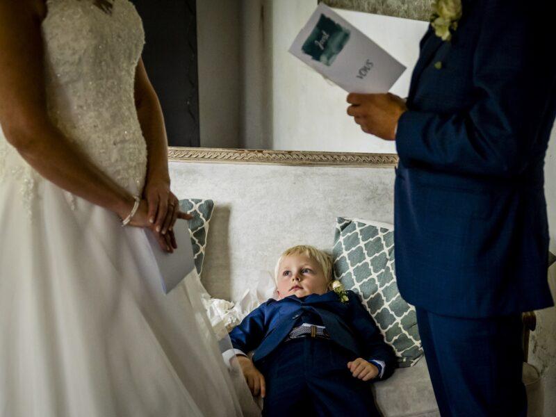 Bruidsjonker ligt op bank en kijkt verveeld naar ouders. Fotograaf Karin Keesmaat van Kijk-Kunst fotografie