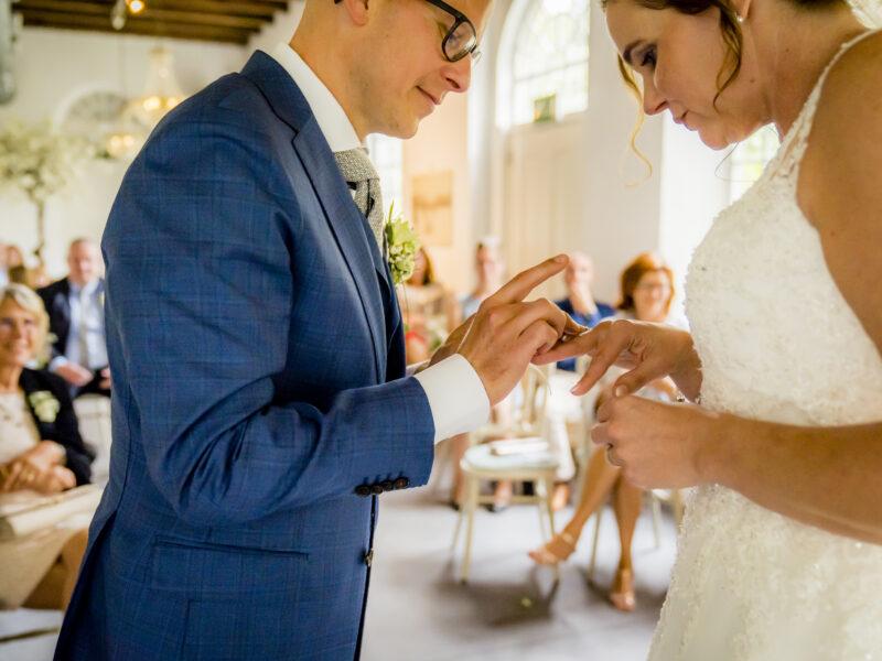 Bruidegom schuift ring om vinger bruid. Fotograaf Karin Keesmaat van Kijk-Kunst fotografie