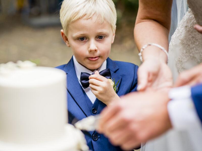 Bruidsjonker steekt tong uit bij zien van bruidstaart. Fotograaf Karin Keesmaat van Kijk-Kunst fotografie