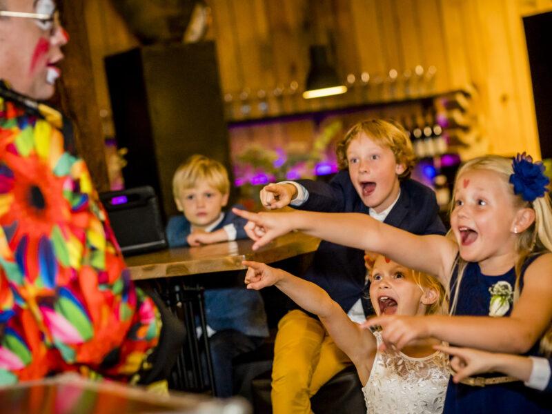 Kinderen op bruiloft wijzen naar clown/goochelaar. Fotograaf Karin Keesmaat van Kijk-Kunst fotografie