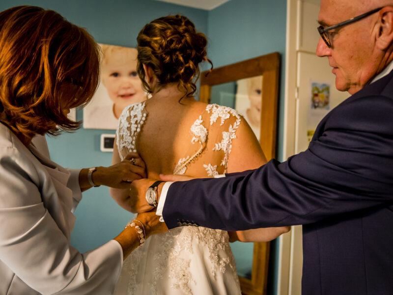 Moeder doet knoopjes van de bruidsjurk dicht en vader helpt mee. Fotograaf Karin Keesmaat van Kijk-Kunst fotografie
