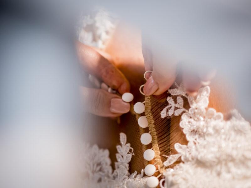 Knoopjes van de bruidsjurk worden dichtgedaan. Fotograaf Karin Keesmaat van Kijk-Kunst fotografie