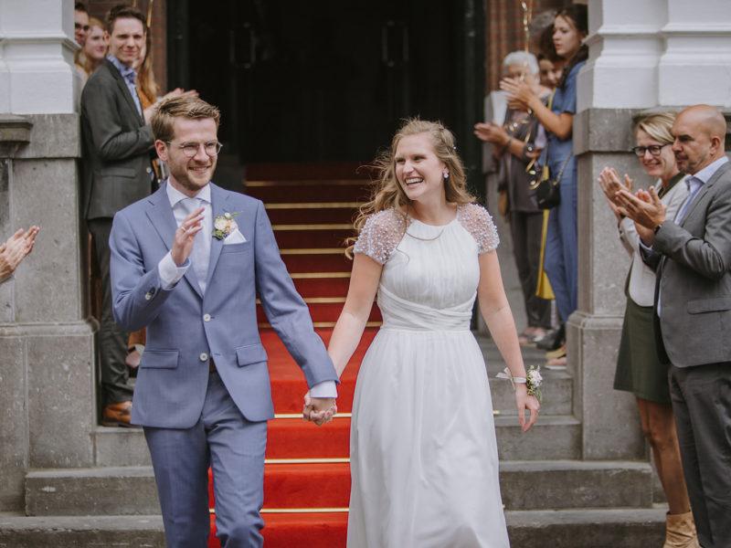 Bruid en bruidegom lopen door haag op afstand vanwege corona. Bruiloft Christiaan en Lydia, foto d-eYe photography