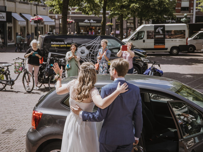 Bruid en bruidegom kijken wie op Raadhuisplein staan. Bruiloft Christiaan en Lydia, foto d-eYe photography