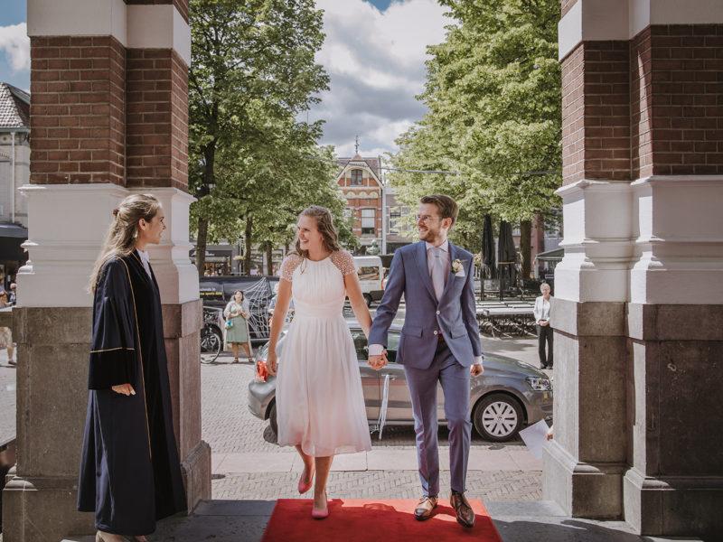 Bruid en bruidegom lopen over rode loper Raadhuis Apeldoorn, met Elise Teunissen trouwambtenaar. Bruiloft Christiaan en Lydia, foto d-eYe photography