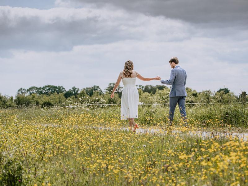 Bruid en bruidegom lopen op pad tussen bloemen. Bruiloft Christiaan en Lydia, foto d-eYe photography