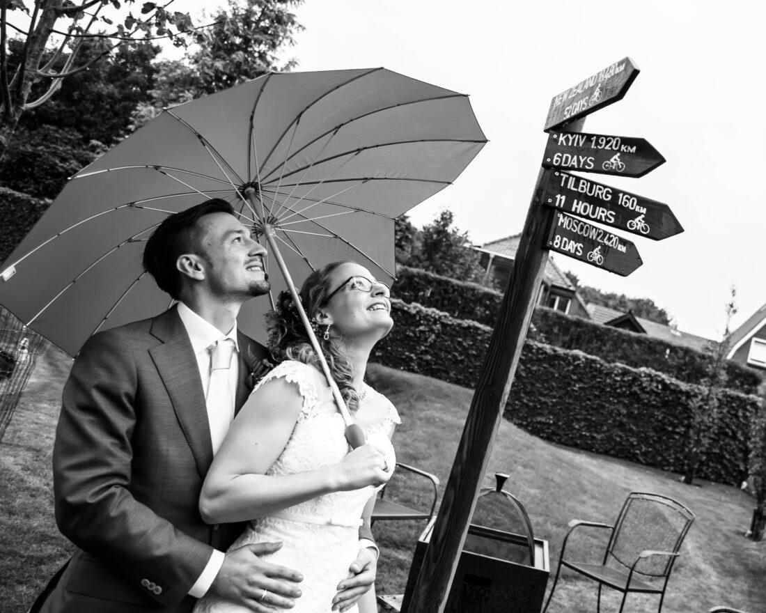Bruidspaar trouwt in eigen tuin, onder paraplu. Foto: Jacqueline Sibon