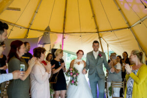 Bruidspaar loopt over gangpad in tent. Foto: Karin Keesmaat van Kijk-Kunst fotografie